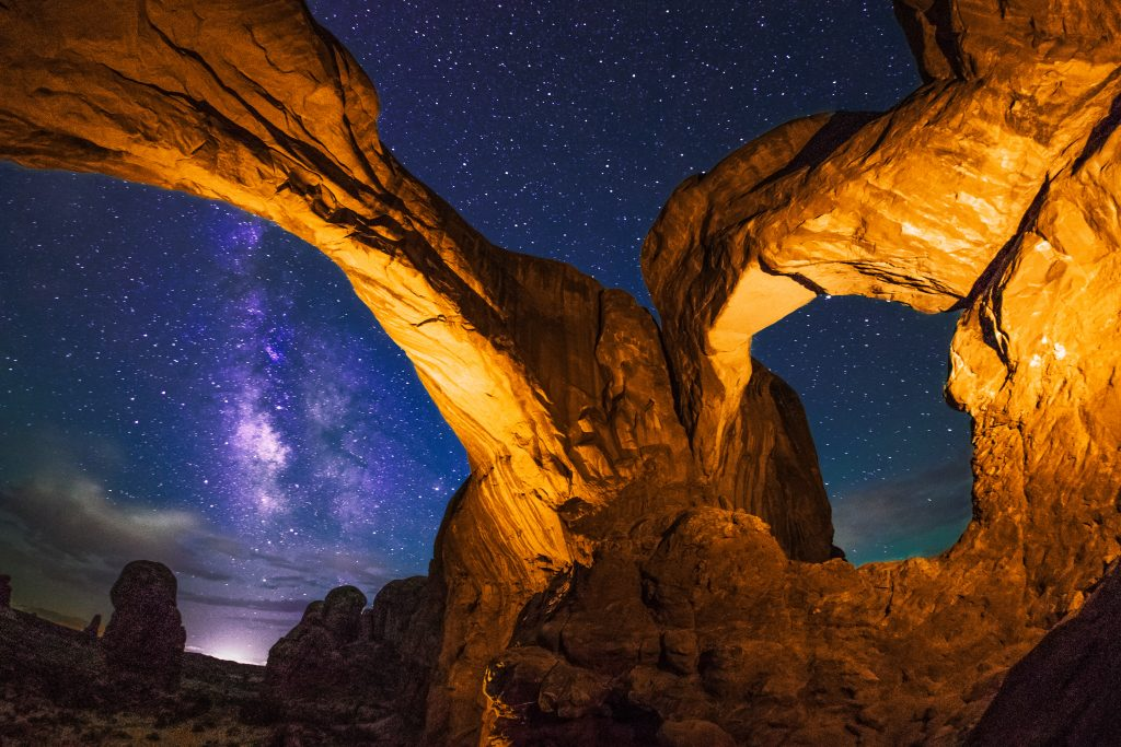 The view looking out of Double Arch at night, with the Milky Way. Arches National Park, Utah, USA. Taken with a Sigma 15mm fisheye lens.