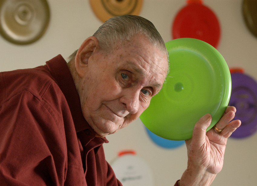 "This photo provided by Wham-O shows Frisbee inventor Walter F. Morrison holds a re-issue of the Pluto Platter Frisbee disc Thursday, Dec. 28, 2006, in Carpinteria, Calif. The original Pluto Platter Frisbee disc, designed by Morrison, made its debut in 1957. Wham-O is celebrating Frisbee's 50th anniversary by re-releasing this historic flying disc. (AP Photo/Wham-O, John Hayes) ** NO SALES ** Walter Fredrick Morrison - der Erfinder der Flugscheibe, die nicht nur Kinder begeistert - am 28. Dezember 2006 mit einer Neuauflage des ""Pluto Platter"". Dieses Frisbeemodell wurde erstmals 1957 vertrieben. Erst 1959 änderte der US-Spielwarenhersteller Wham-O den Markennamen offiziell in ""Frisbee"" um."